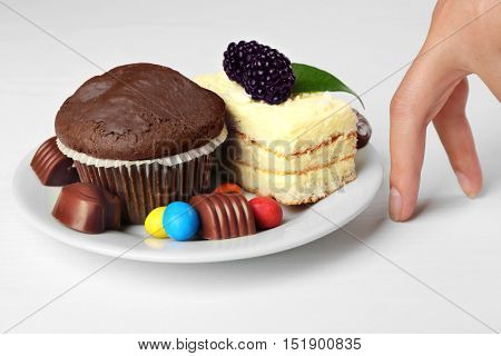 Female hand and plate with tasty sponge-cake, chocolate muffin and sweets on white table. Diet interruption concept
