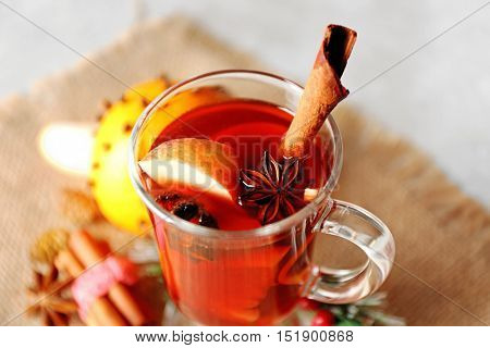 Glass cup of delicious Christmas mulled wine on sackcloth, closeup