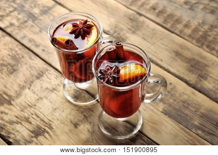 Glass cups of delicious Christmas mulled wine on wooden background