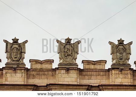 Fragment of parapet administrative government building with USSR symbols . Emblems with the hammer and sickle, a sheaf. Typical pattern of Stalinist architecture.