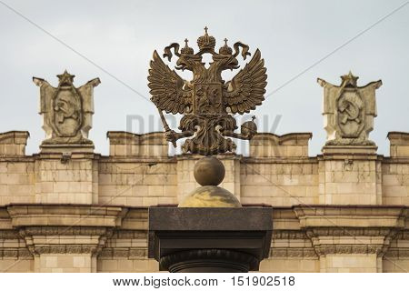 Coat of arms of the Russian Federation. Coat of arms on the background of the parapet of the administrative government building with Soviet symbols. Focus on the two-headed eagle.