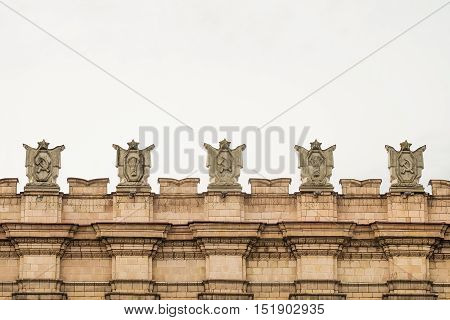 Fragment of parapet administrative government building with USSR symbols . Emblems with the hammer and sickle a sheaf. Ornament of the Stalinist Empire style of architecture.