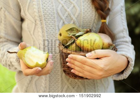 Woman holding basket full of green pears