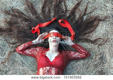 The woman lies on straw her eyes are closed by a red tape and hair are scattered.