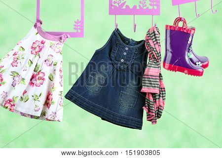 Fashion baby dresses hanging on a hanger on a green background