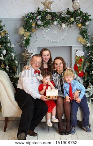 Mother, father, son and daughter hold gingerbread house during christmas