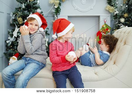 Three happy children in santa caps sit on couch with balls near Christmas trees, focus on blonde boy