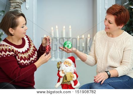 Two women sit on floor with christmas balls near fireplace with candles
