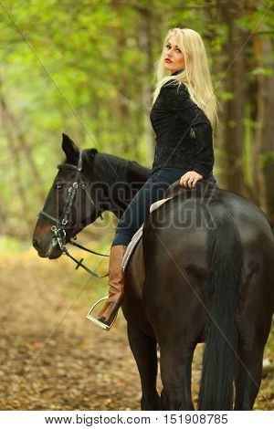Blonde beautiful woman in black rides horse in green autumn park