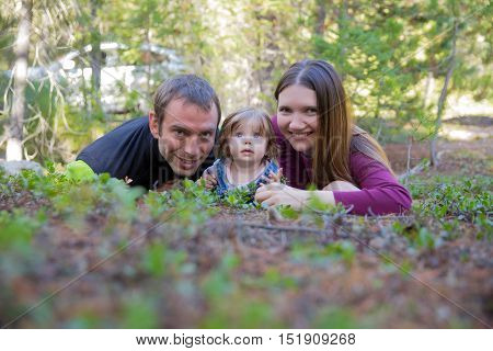 Happy Family With Toddler Girl Lying On The Ground In The Forest