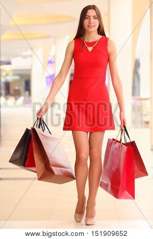 Beautiful smiling girl in short dress goes with bags in shopping center