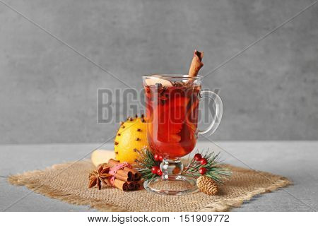 Glass cup of delicious mulled wine with Christmas decor on sackcloth