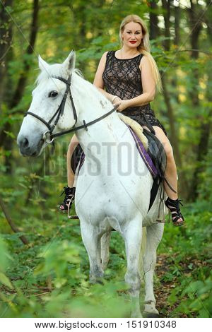 Woman in long black dress sits on beautiful white horse in green park