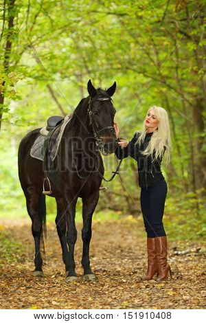 Pretty young blonde woman stands near whire beautiful horse in autumn park