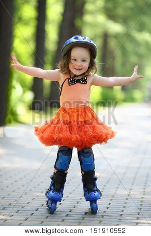 Little happy girl in skirt and helmet roller-blades in park at summer day