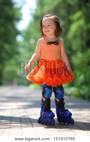 Little girl in skirt roller-blades and smiles in park at summer day