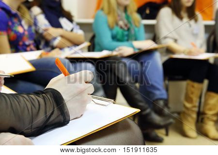 Listener hand writes on sheet during training, women knees out of focus