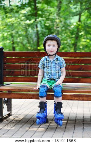Little handsome boy in roller-blades sits on bench in sunny park