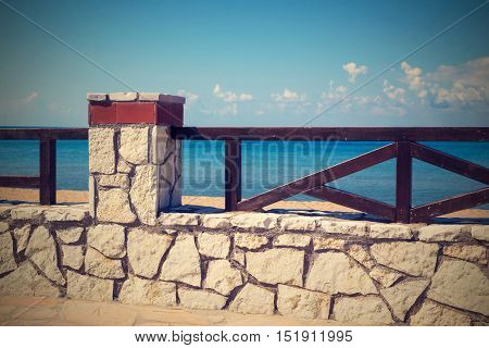 architecture of the stone embankment or seafront with a fence closeup in retro style