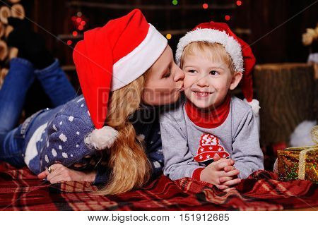 Mom and baby in red Christmas caps lying on a red plaid. Mum kisses the cheek of her child on the background of Christmas lights