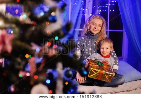 mother and son smiling with Christmas present in hands on the background of Christmas lights and Christmas tree.