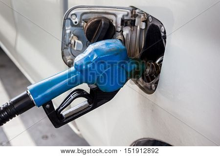 refilling fuel in the car with dirty blue nozzle at gas station