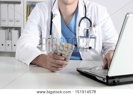 Male Doctor Sitting At The Table And Holding Bottle