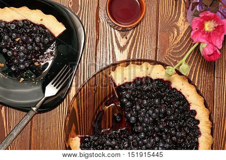 Bilberry cake on plate on wooden table. Rustic style