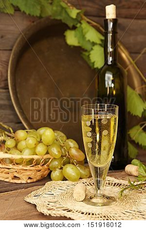 Vintage Wine Glass Against Background Cluster Of Grapes And Wine Bottle
