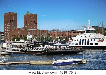 OSLO NORWAY - AUGUST 17 2016: People walking on modern district on street Stranden Aker Brygge district and in the background is the City Hall in Oslo Norway on August 172016.
