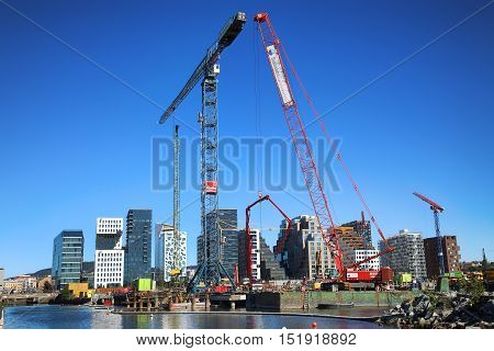 OSLO NORWAY - AUGUST 17 2016: A construction site of Bjorvika under construction in progress with a heavy vehicle and cranes in Oslo Norway on August 172016.