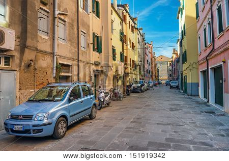 Chioggia - January 2015, Italy: Cars parked near traditional colored houses in Venetian style on one of the streets in historic part of the old Italian city