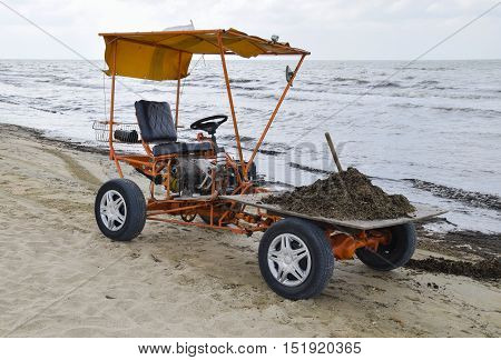 The car for garbage collection from the beach. Cleaning on the beach clean beach from mud and waste.