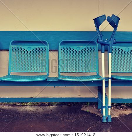 Medical Crutch At Blue Metal Seats On Outdoor Stadium Players Bench