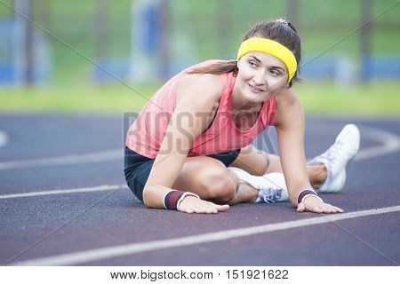 Positive Caucasian Sporstwoman Having Stretching Exercises On Stadium Outdoors.Horizontal Composition