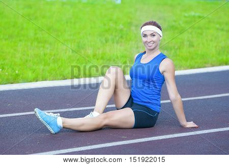 Portrait of Smiling Happy Caucasian Female Athlete During Body Stretching Exercises Outdoors. Horizontal Composition