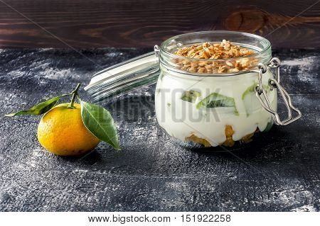Sweet parfait with kiwi, yogurt and muesli on dark table