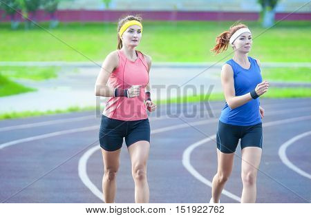 Jogging Concepts. Two Young Caucasian Athletes Running Closely to Each Other Outdoors. Horizontal Image
