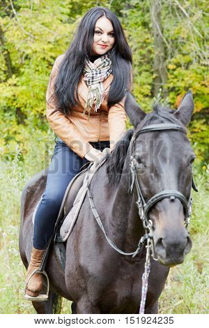 Black-haired woman in brown jacket sits on bay horse in park.