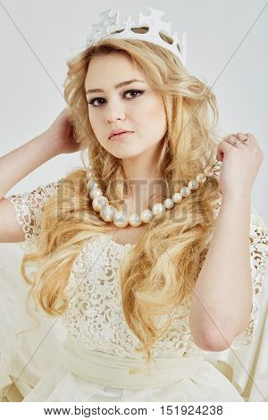 Young blond woman in crown holds beads of big artificial pearls around her neck.