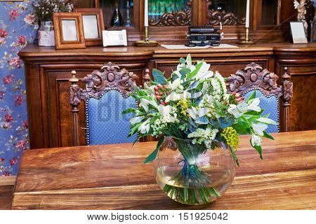 Bunch of flowers in jug on table in old-fashioned style room.