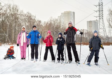 Group of seven people three adults and four children on skis and sledge across snowy lawn.