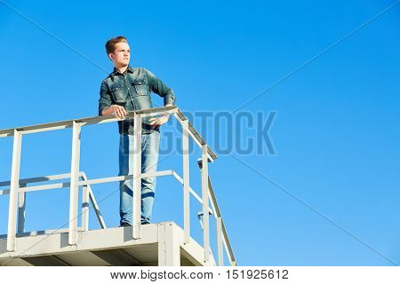 Young man in denim wear stands on metal construction against blue sky and looks into the distance.