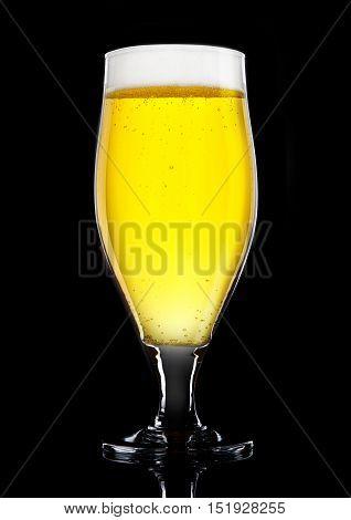 Glass of beer cider with foam golden color on black background