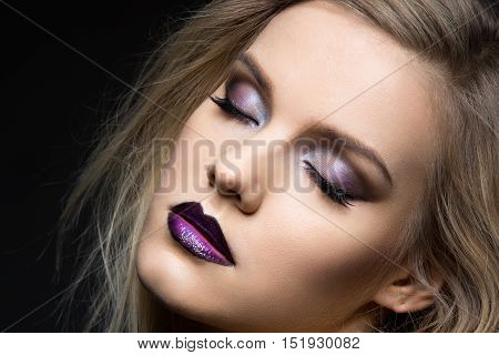 Beautiful young woman with dark purple eye make-up and lips. Modern fluffy styled blond hair. Closeup studio beauty shot over black background. Copy space.