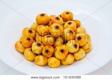 yellow ripe hawthorn in a white plate on a background. in a studio