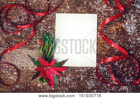 Christmas holiday background with red poinsettia flower decoration and ribbon with white blank for your text