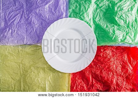 White plate over colorful tissue paper background. Flat lay