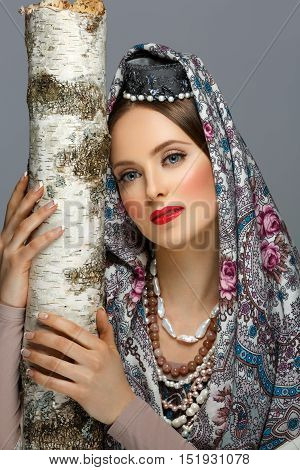 Beautiful young woman with make-up in traditional Russian clothes hugging birch tree. Pearl accessories, hat and shawl. Over grey background. Copy space.