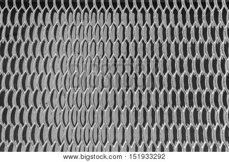Galvanized steel grating on the background of a concrete wall